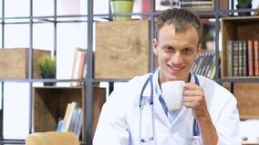 Portrait du docteur de sourire ayant une pause-café dans la salle du personnel photos stock