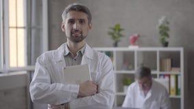 Portrait du docteur de sourire beau regardant dans le comprimé de participation de caméra sur le fond de son collègue dans clips vidéos