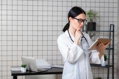 Portrait du docteur féminin à l'aide de son comprimé numérique dans le bureau photographie stock
