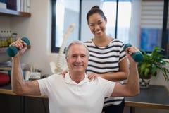 Portrait du docteur féminin de sourire se tenant avec les haltères de levage patientes masculines Photographie stock