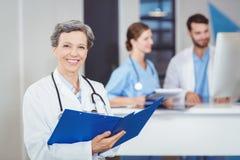 Portrait du docteur féminin heureux tenant des rapports médicaux Photo stock