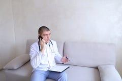 Portrait du docteur masculin responsable qui communique sur la cellule et Photo stock