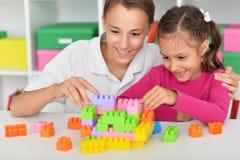 Portrait du frère et de la soeur jouant avec les blocs en plastique colorés ensemble image stock