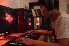 Portrait du garçon adolescent asiatique de gamer perdant tout en jouant la vidéo g image stock