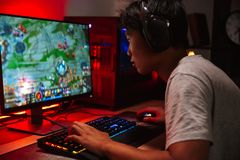 Portrait du garçon asiatique de gamer jouant des jeux vidéo sur l'ordinateur dans d photo stock