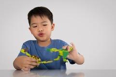 Portrait du garçon asiatique mignon jouant avec le bri en plastique coloré de jouet photographie stock libre de droits