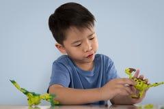 Portrait du garçon asiatique mignon jouant avec le bri en plastique coloré de jouet images libres de droits