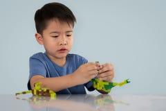 Portrait du garçon asiatique mignon jouant avec le bri en plastique coloré de jouet images stock