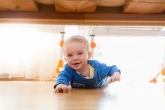 Portrait du garçon de sourire mignon d'enfant en bas âge se trouvant sur le plancher et regardant sous le lit Image stock