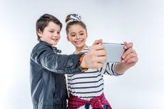Portrait du garçon et de la fille de sourire faisant le selfie Images stock