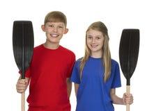 Portrait du garçon et de la fille tenant la palette de canoë Image stock