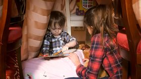 Portrait du garçon mignon d'enfant en bas âge s'asseyant dans la tente au livre de chambre à coucher et de lecture Photo stock