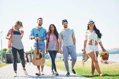 Portrait du groupe d'amis allant à sur la plage Groupe mixte d'amis marchant sur la plage le jour d'été Image libre de droits