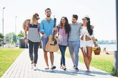 Portrait du groupe d'amis allant à sur la plage Groupe mixte d'amis marchant sur la plage le jour d'été Photographie stock