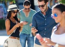 Portrait du groupe d'amis ayant l'amusement avec des smartphones Photos stock