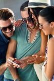 Portrait du groupe d'amis ayant l'amusement avec des smartphones Photo libre de droits