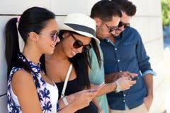 Portrait du groupe d'amis ayant l'amusement avec des smartphones Image libre de droits