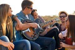 Portrait du groupe d'amis jouant la guitare et buvant de la bière Photo stock