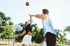 Portrait du groupe d'amis jouant le basket-ball sur la cour Images libres de droits