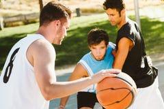 Portrait du groupe d'amis jouant le basket-ball sur la cour Photos libres de droits