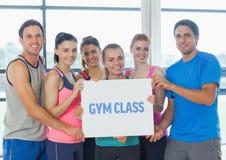 Portrait du groupe de personnes heureuses tenant la plaquette vide dans le gymnase Photos stock