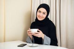 Portrait du hijab de port de femme asiatique attirante appréciant le café et souriant à l'appareil-photo photographie stock libre de droits
