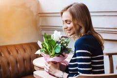 Portrait du hippie féminin de sourire s'asseyant en café et tenant le bouquet de ressort Cadeau de fleur d'ami gris Photo stock