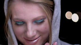 Portrait du jeune blond dans le hoodie avec le maquillage coloré lumineux souriant avec satisfaction sur les lumières brouillées banque de vidéos