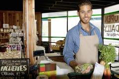 Portrait du jeune commis de magasin beau jugeant végétal dans le supermarché images libres de droits