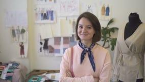 Portrait du jeune concepteur féminin de fasion, qui pose pour la photo dans son studio, mouvement lent banque de vidéos