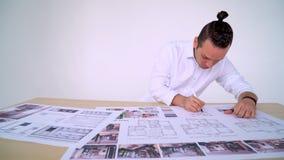 Portrait du jeune concepteur qui travaille au bureau avec le dessin, la règle et le crayon L'homme dans un chandail tient des fou banque de vidéos