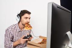 Portrait du jeune gamer masculin beau jouant des jeux d'ordinateur avec le contrôleur dans des écouteurs, tenant la pizza dans la photographie stock libre de droits
