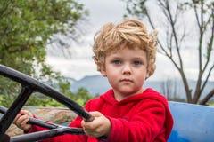 Portrait du jeune garçon blond sérieux s'asseyant sur une exploitation de tracteur Photographie stock