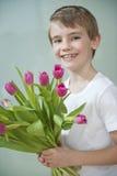 Portrait du jeune garçon heureux tenant le groupe de tulipes roses sur le fond gris Photos libres de droits