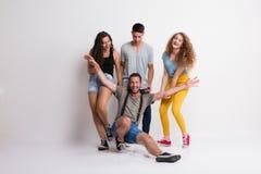 Portrait du jeune groupe joyeux d'amis se tenant dans un studio photographie stock libre de droits