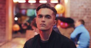 Portrait du jeune homme attirant au café de nuit souriant et regardant dans la caméra Lumières de soirée à l'arrière-plan banque de vidéos