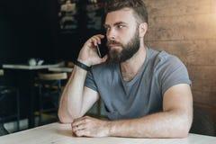 Portrait du jeune homme barbu bel sérieux de hippie s'asseyant en café à la table et parlant à son téléphone portable Images stock