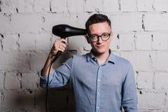 Portrait du jeune homme beau dans des vêtements et des lunettes de jeans avec le hairdryer regardant à l'appareil-photo souriant, Image stock