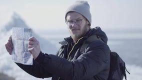 Portrait du jeune homme bel barbu blond portant la position chaude de veste et de chapeau sur le glacier vérifiant avec la carte banque de vidéos
