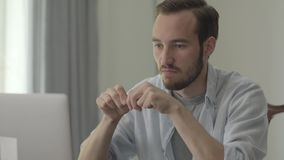 Portrait du jeune homme bel cassant le crayon avec colère se reposant devant son ordinateur dans le bureau Problèmes à clips vidéos
