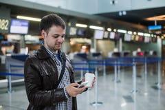 Portrait du jeune homme bel marchant dans le terminal d'aéroport moderne, service de mini-messages, voyageant avec le sac et le c Photos stock