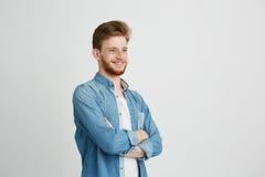 Portrait du jeune homme bel sûr gai avec la barbe souriant au-dessus du fond blanc Bras croisés Photos stock