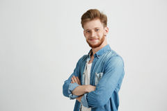 Portrait du jeune homme bel sûr souriant regardant l'appareil-photo avec les bras croisés au-dessus du fond blanc Photo stock