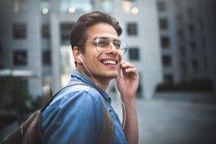 Portrait du jeune homme bien habillé bel gai avec des écouteurs pensant au nouveau projet photographie stock
