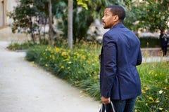 Portrait du jeune homme d'affaires afro-américain sûr heureux dans le tenue de soirée marchant au parc de ville avec le sac de vo photographie stock libre de droits