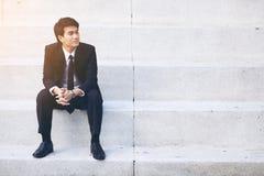 Portrait du jeune homme d'affaires bel de sourire s'asseyant sur les escaliers Image libre de droits