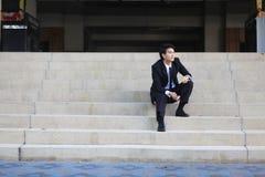 Portrait du jeune homme d'affaires bel de sourire s'asseyant sur les escaliers Photo stock