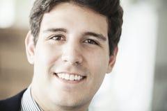 Portrait du jeune homme d'affaires de sourire regardant l'appareil-photo, principal et les épaules Photos stock