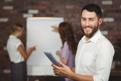 Portrait du jeune homme d'affaires de sourire tenant le comprimé numérique Photo stock