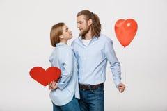 Portrait du jeune homme et de la femme tenant un ballon et un papier en forme de coeur Photos libres de droits